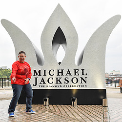 © Licensed to London News Pictures. 29/08/2018. LONDON, UK. A Michael Jackson fan dances next to a 13 foot high jewelled crown which has been installed on the South Bank to mark Michael Jackson's 60th birthday.  Photo credit: Stephen Chung/LNP