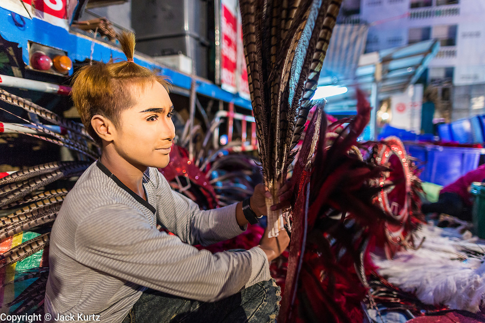 19 JANUARY 2014 - BANGKOK, THAILAND:  A member of the cast cleans the feathers on his headdress before a mor lam show in Khlong Tan Market in Bangkok. Mor Lam is a traditional Lao form of song in Laos and Isan (northeast Thailand). It is sometimes compared to American country music, song usually revolve around unrequited love, mor lam and the complexities of rural life. Mor Lam shows are an important part of festivals and fairs in rural Thailand. Mor lam has become very popular in Isan migrant communities in Bangkok. Once performed by bands and singers, live performances are now spectacles, involving several singers, a dance troupe and comedians. The dancers (or hang khreuang) in particular often wear fancy costumes, and singers go through several costume changes in the course of a performance. Prathom Bunteung Silp is one of the best known Mor Lam troupes in Thailand with more than 250 performers and a total crew of almost 300 people. The troupe has been performing for more 55 years. It forms every August and performs through June then breaks for the rainy season.              PHOTO BY JACK KURTZ