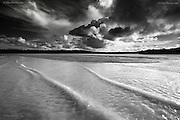 Waves from gentle surf approaching Traeth (beach) Lligwy at East Anglesey in dramatic, squally, rainy weather, with dramatic slouds in the sky.