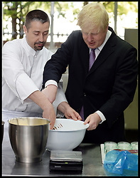 London Mayor Boris Johnson eating a Gü chocolate soufflé during a visit with the Gü head chef Fred, at the Gü development kitchen, Gü Puds, London, UK,  May 2, 2013..The Mayor Boris Johnson will announce details of a £40million fund to support jobs and enterprise in the capital. This money will help drive the delivery of a new jobs and growth strategy developed by the London Enterprise Panel with particular focus on small and medium businesses, May 2, 2013. Photo by: Andrew Parsons / i-Images