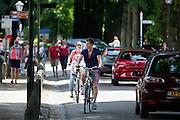 In Lage Vuursche rijdt een gezin op de fiets door de drukke Dorpsstraat.<br /> <br /> In Lage Vuursche a family is cycling in the crowded street.