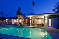 Illuminated swimming pool and villa at night