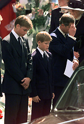 File photo dated 6/9/1997 of Prince William, Prince Harry and Prince Charles watching as the coffin containing the body of Diana, Princess of Wales, is driven away from Westminster Abbey after her funeral service.