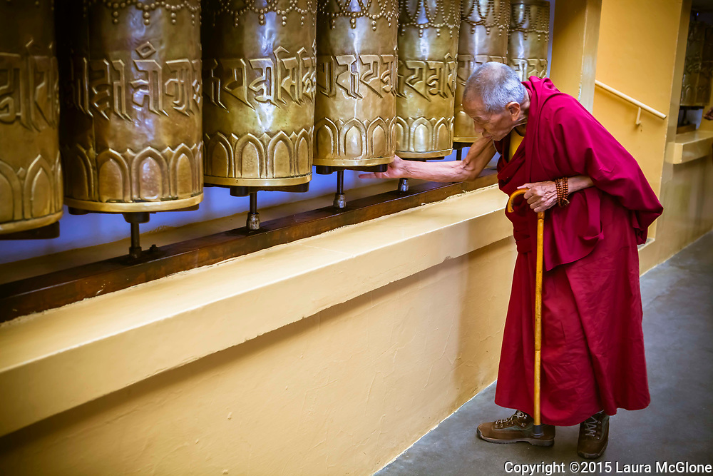 Monk Elder turning prayer wheels at the Dalai Lama's temple, Dharamsala, India