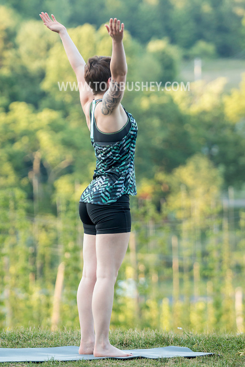 Westtown, New York - A woman  participates in a Wild Soul Yoga Studio sunset yoga session at Westtown Brew Works on July 21, 2016.