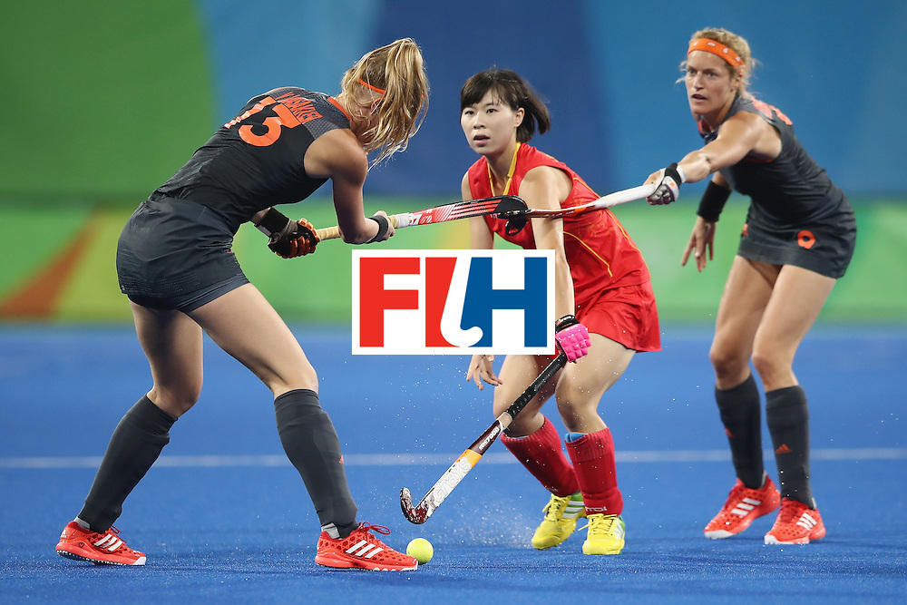 RIO DE JANEIRO, BRAZIL - AUGUST 10:  Caia van Maasakker and Carlien Dirkse van den Heuvel of the Netherlands hook sticks as Jinrong Zhang of China looks on during the women's pool A match between China and the Netherlands on Day 5 of the Rio 2016 Olympic Games at the Olympic Hockey Centre on August 10, 2016 in Rio de Janeiro, Brazil.  (Photo by Mark Kolbe/Getty Images)