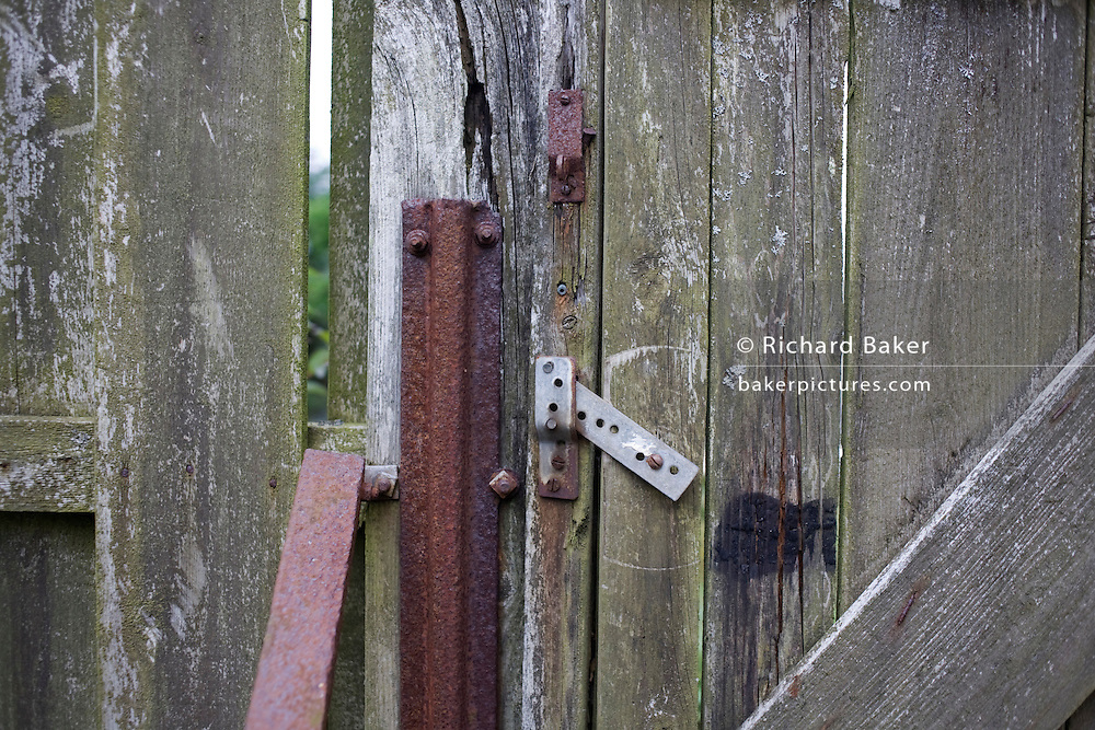Rusting metal stakes and locks in back garden gate in hamlet of Waterloo, Isle of Skye, Scotland.