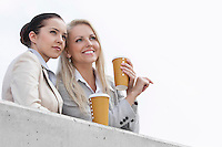 Low angle view of businesswomen with disposable coffee cups looking away while standing on terrace against sky