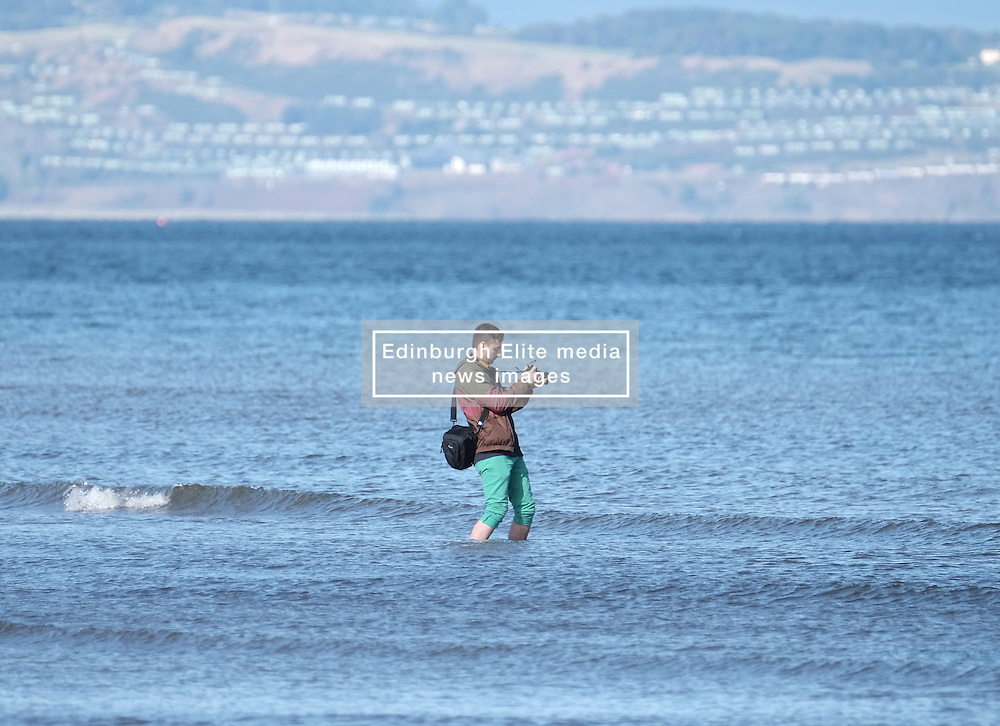 A photographer paddles in the sea at Portobello Beach in Edinburgh during a sunny first day of Autumn.<br /> <br /> Edinburgh Weather Pictures, Thursday 22nd September 2016<br /> <br /> (c) Alex Todd | Edinburgh Elite media