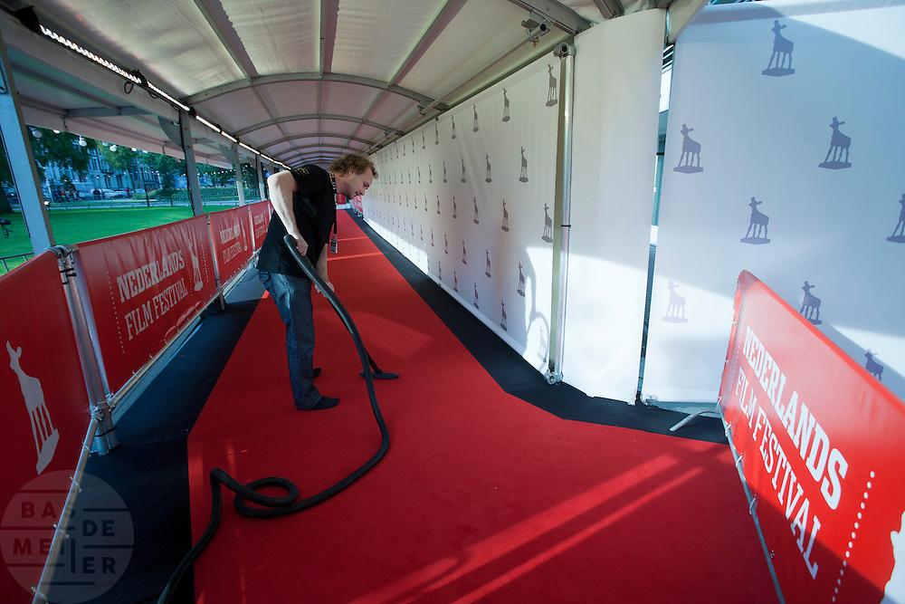 Een medewerker van het Nederlands Film Festival stofzuigt de rode loper.<br /> <br /> A man is cleaning the red carpet at the Nederlands Film Festival