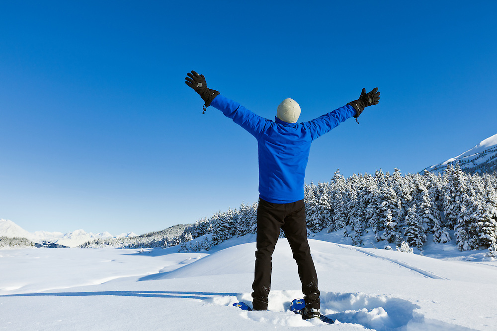 A hiker on snowshoes holds up his arms and expresses exuberance at the sunny blue-sky weather at Turnagain Pass in the Chugach National Forest of Southcentral Alaska. Winter. Afternoon. MR.