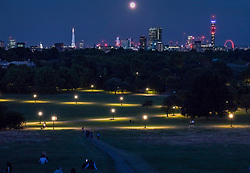 © Licensed to London News Pictures. 28/06/2018. London, UK. People watch from Primerose Hill as a spectacular full moon, known as the strawberry moon, rises after another hot summer day in the capital. Photo credit: Peter Macdiarmid/LNP