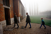 Three members of a French family walk into their local Catholic church in rural Normandy early on a misty morning.