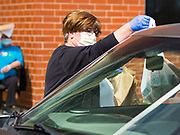 22 APRIL 2020 - DES MOINES, IOWA: SUSAN AYALA hands a grab and go meal to people in a car at Edmunds Elementary School. Schools in Iowa are closed for the rest of the school year because of the COVID-19 (Coronavirus/SAR-CoV-2) pandemic. Des Moines Public Schools expanded their school lunch and distance learning efforts this week. Lunches are being distributed at all of the district's elementary and middle schools and officials have started distributing computers so students can participate in distance learning. The meal distribution was done according to social distancing guidelines.          PHOTO BY JACK KURTZ