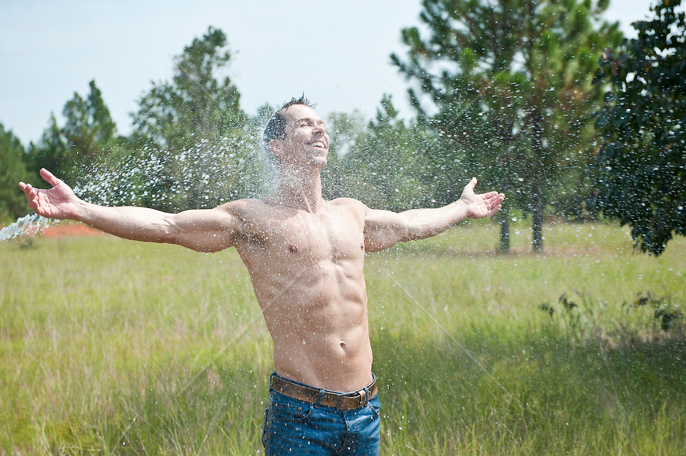 man enjoying being hosed down while standing outdoors in nature