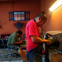 """081613  Adron Gardner/Independent<br /> <br /> Stone setter Lester James, right, woks the polishing wheel with Aaron Anderson, left,  in Gallup Friday. """"Lester can fix anything,"""" Anderson said."""