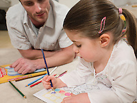Girl on Floor Coloring With Father