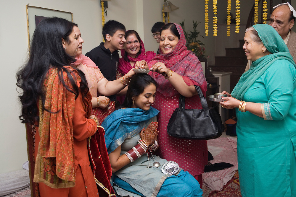 New Delhi, India, January 21, 2011. Sumedha and Sapan Wedding. Propitiatory celebrations for the bride together with the women from the family.