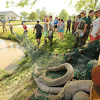 Students begin dragging the net into place before getting into the water to start harvesting catfish for the Private John Allen Fish Hatchery Thursday.