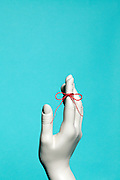 red string tied around female mannequin finger symbolic for remembering