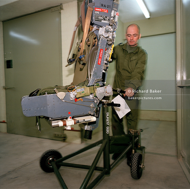 Corporal Mal Faulder pushes a Martin-Baker ejection seat through an RAF Hangar. He is an Armourer (an engineer handling seats and weaponry on military jets) but here in the elite 'Red Arrows', Britain's Royal Air Force aerobatic team, his duties are wider. With other members of the team's support staff (the Blues who outnumber the pilots the Reds by 8 to 1) he also helps clean the Hawk aircraft before air shows across the country. He pulls the seat into a blast-protected bunker for safe storage where explosive charges inside this equipment are temporarily removed. The seat is returned to service when the aircraft is through its regular maintenance schedule. British company Martin-Baker manufacturers ejection seats and membership of the its Tie Club is solely for air crew who have ejected from an aircraft in an emergency which saved their life.