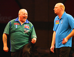 England's Andy Hamilton, left,  celebrates beating Vincent van der Voort of the Nrtherland's, right, 4-3 to move to the next round in the Darts World Championships at Alexandra Palace, London, Tuesday, Dec.. 27, 2011. photo by morn/I-Images