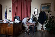 27 Febbraio 2015, Reggio Calabria, Italia. Un collaboratore del primo cittadino di Reggio Calabria, Giuseppe Falcomatà, a lavoro su documenti nella stanza del Sindaco.