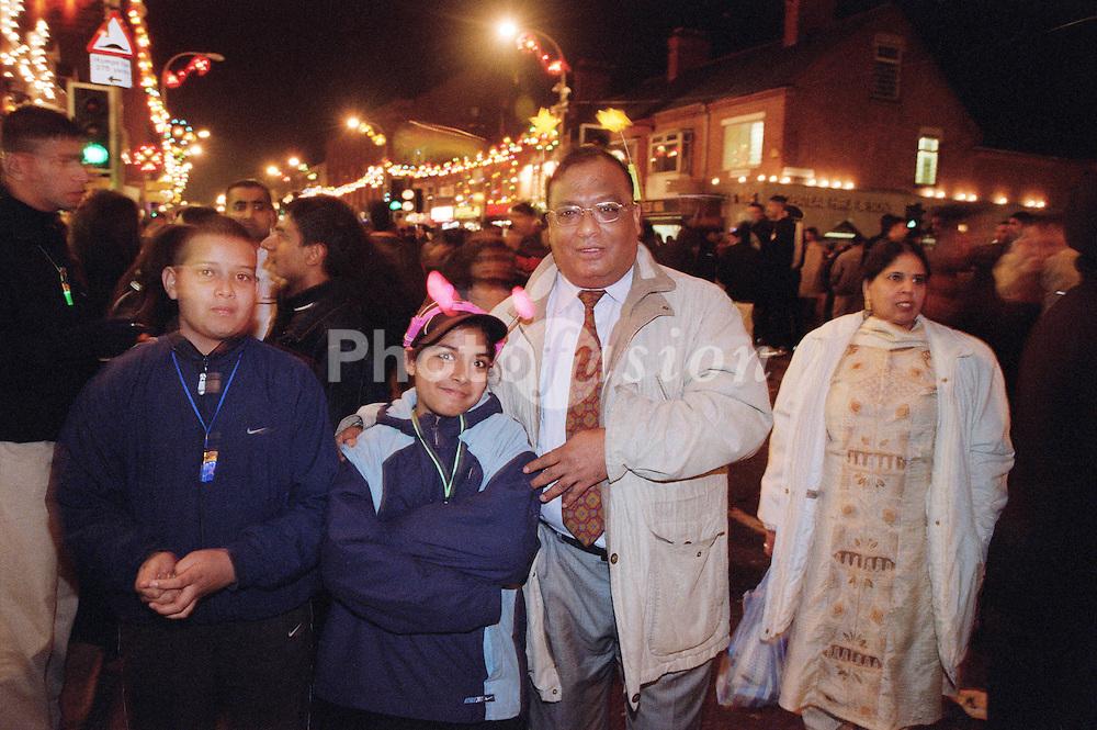 Family group standing together in street celebrating Diwali; festival of light,