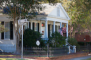 Quaint clapboard 19th Century cottage style house with Stars and Stripes flag, South Canal Street in Natchez, Mississippi, USA