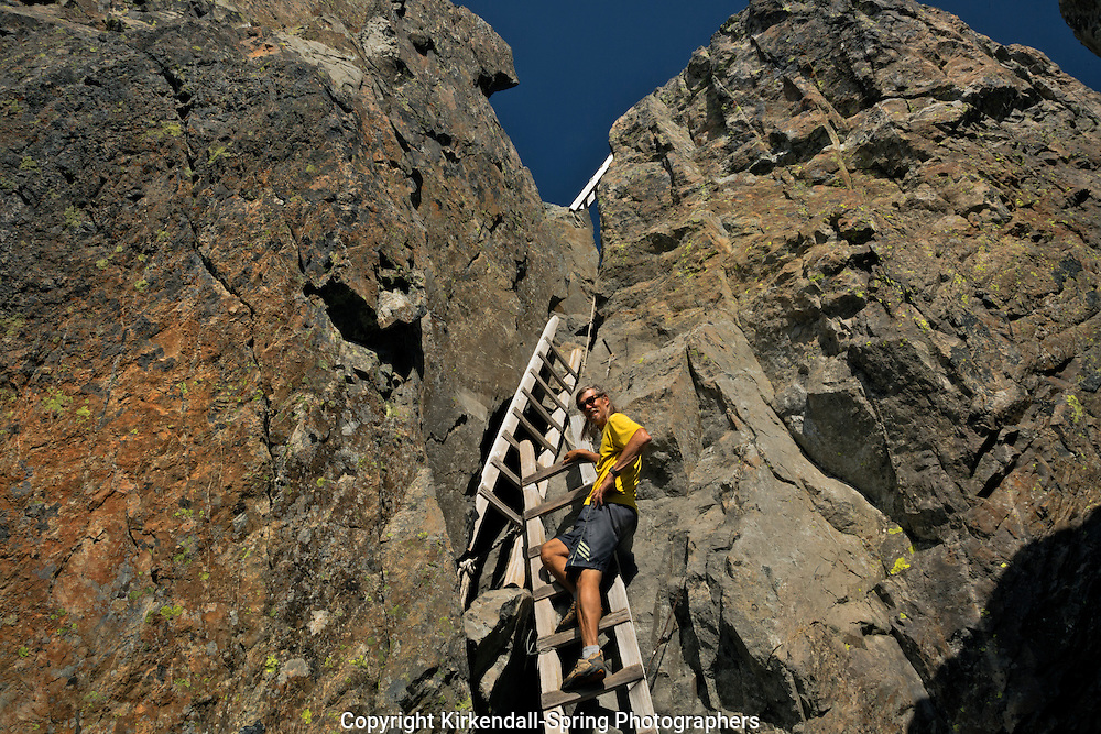 WA10793-00...WASHINGTON - Hiker on the sturdy ladders used to access the fire lookout located on the summit of the South Peak of Three Fingers in the Boulder River Wilderness area of Mount Baker-Snoqualmie National Forest.