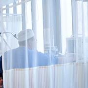 Nederland Rotterdam  25-08-2009 20090825 Foto: David Rozing .Serie over zorgsector, Ikazia Ziekenhuis Rotterdam. ..Foto: David Rozing Serie over zorgsector, Ikazia Ziekenhuis Rotterdam. Een verpleegkundige controleert een patient op de recoveryroom, dit is een zaal waar patienten na een operatie verzorgd worden. Patient is being checked by doctor, in recovery room, where people are looked after, after surgery. ziekenzaal, op zaal liggen Holland, The Netherlands, dutch, Pays Bas, Europe, professionele, professional, steriel, steriele omgeving, werkkleding, kledingvoorschriften, , genezen, genezing, ziekte bestrijding bestrijden, ernstig ziek zijn, , illustratief beeld; illustratieve; illustrative image,stock; stockbeeld; symbolisch beeld; symbolic..Foto: David Rozing..Holland, The Netherlands, dutch, Pays Bas, Europe, ronde doen, routine verpleegkundigen, op zaal liggen ziekenhuiszaal behandelplan, treatment,.,ziektekosten,zorgverlener, zorgverleners,zorgverlening, achter gordijnen,verpleger, verplegers, verplegend, status