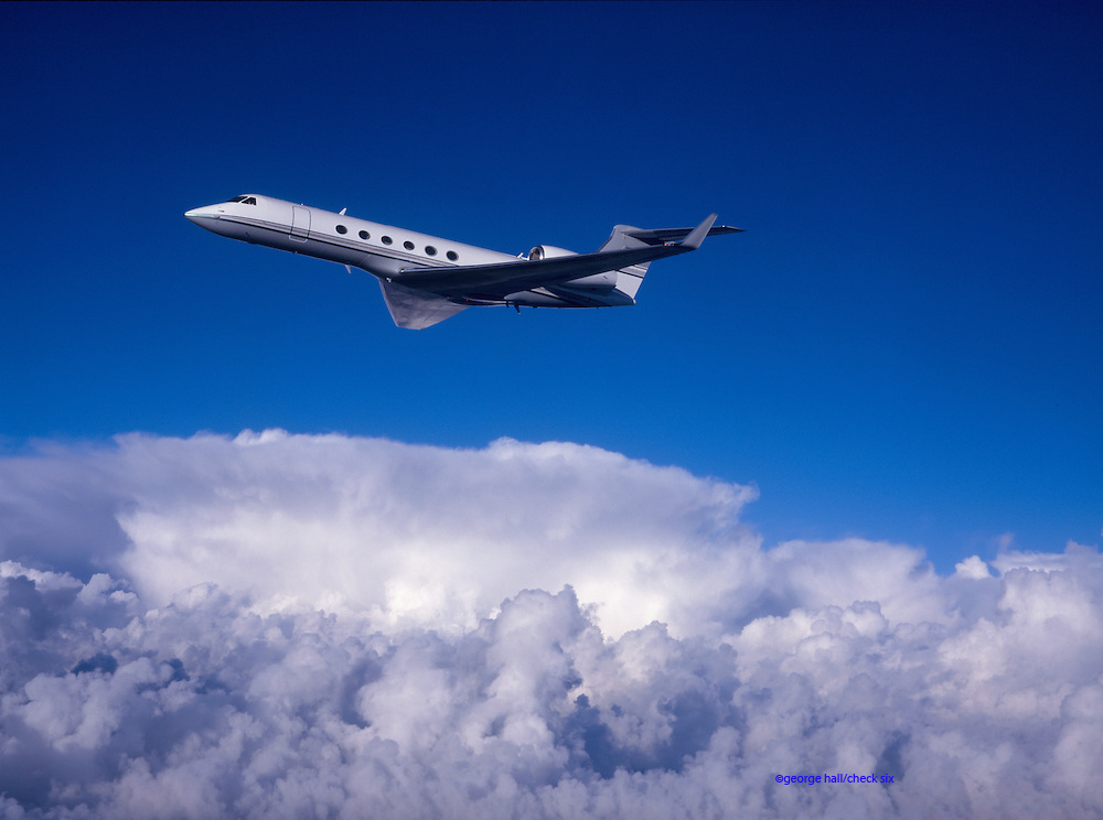 Gulfstream G-V business jet in flight over the clouds