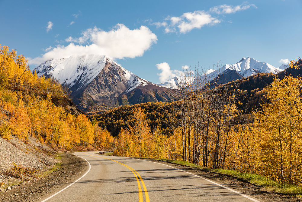 Termination dust contrasts with fall colors and blue skies along the Glenn Highway along the Matanuska Valley in Southcentral Alaska. Afternoon.
