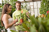Couple Selecting Flowering Plant at Greenhouse
