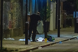 © Licensed to London News Pictures. 26/06/2020. London, UK. A forensic investigator uses a torch to look for evidence around medial kits left by paramedics indicated by an evidence identification marker inside the police cordon. A person has been stabbed on Du Cane Road in East Acton on Thursday 25th June 2020. A cordon closed off a large section of the road underneath a railway bridge where two vehicles remained. Photo credit: Peter Manning/LNP
