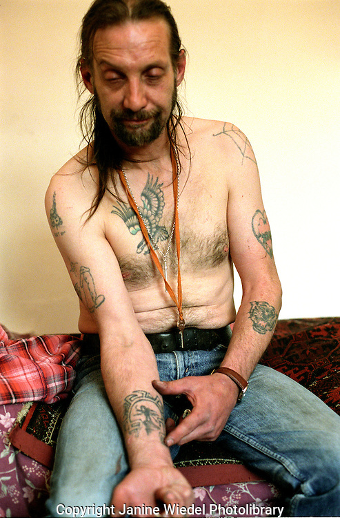 Addict at home in his room with tattoos