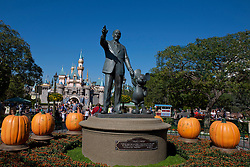 View of the Partners statue of Walt Disney and Mickey Mouse with Sleeping Beauty Castle in the background, decorated for Halloween, Disneyland, Anaheim, California, United States of America