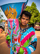 28 JUNE 2014 - DAN SAI, LOEI, THAILAND: A man waits for the ghost festival parade to start in Dan Sai. Phi Ta Khon (also spelled Pee Ta Khon) is the Ghost Festival. Over three days, the town's residents invite protection from Phra U-pakut, the spirit that lives in the Mun River, which runs through Dan Sai. People in the town and surrounding villages wear costumes made of patchwork and ornate masks and are thought be ghosts who were awoken from the dead when Vessantra Jataka (one of the Buddhas) came out of the forest.    PHOTO BY JACK KURTZ