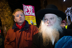 © Licensed to London News Pictures. 30/12/2019. London, UK. Rabbi Herschel Gluck (R) joins people to take part in a protest vigil against anti-semitic graffiti in Hampstead and Belsize Park, held in Rosslyn Hill in Hampstead. Yesterday, anti-semitic graffiti was daubed on a synagogue and several shops in north London during the Jewish festival of Hanukkah. Photo credit: Vickie Flores/LNP