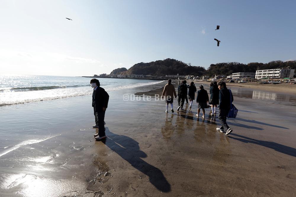 group of school children walking on the beach Japan Kamakura