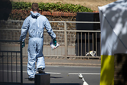 A forensics investigator carries evidence bags as police investigate the killing of a man in his 20s at Cambridge Gardens in Norbiton, Kingston Upon Thames in West London. London, August 05 2018.