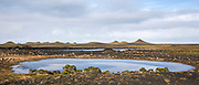 Glacial melt pond at Myrdalssandur, an outwash plain in Vatnajokull National Park, volcanic crater cones behind, South Iceland