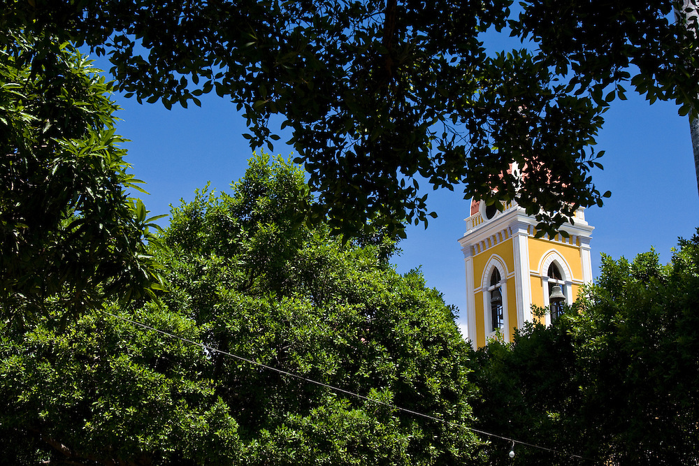 The tower of Granada Cathedral seen through the trees that cover the town square. Granada is Nicaragua's most famous city. founded in 1524 it is one of best examples of Spanish colonial architecture in the Americas. .it has a varied history including its almost total destruction by filibuster William Walker in a childlike tantrum. Today it is a popular tourist town though retains a strong sense of its own identity.