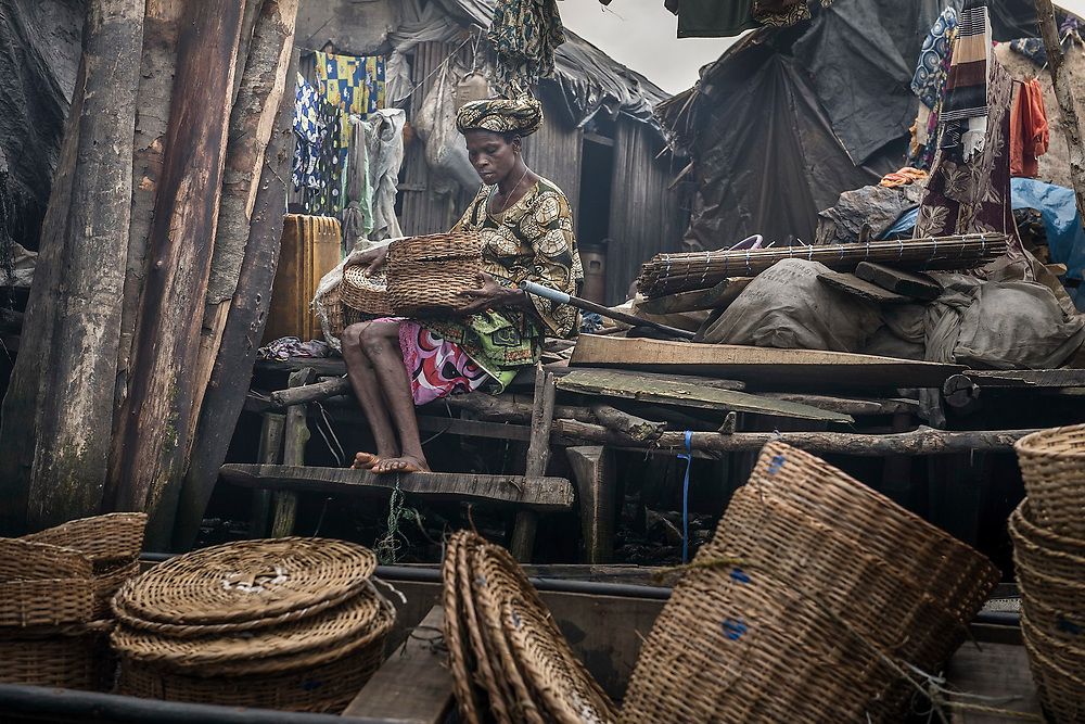A woman who sells baskets, used for moving and storing fish, prepares to take them out for sale in a canoe.