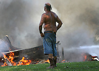 Vince West looks on as his barn burns at 4200 S. Meeker Avenue in Muncie Ind. The barn housed several of West's antique cars. Smoke could be seen for miles around the city and loud explosions were heard at the scene.
