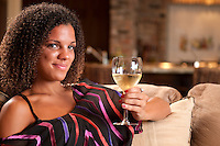 Young woman relaxing in a coach drinking a glass of wine.