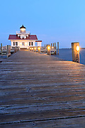 Dock leading up to Roanoke Marshes Lghthouse at twilight.