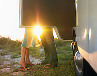 Young couple face to face beside camper van low section