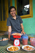 Panglipur Binurissamsika (known as Elip) measuring out some of her home made crisps.<br /> <br /> Elip is 23 years old and runs her own business selling home made crisps, with her friend and business partner is Kirman Nurbin <br /> <br /> Initially they were making a loss but the training course on bookkeeping taught her how to record finances so that she prices her goods appropriately.