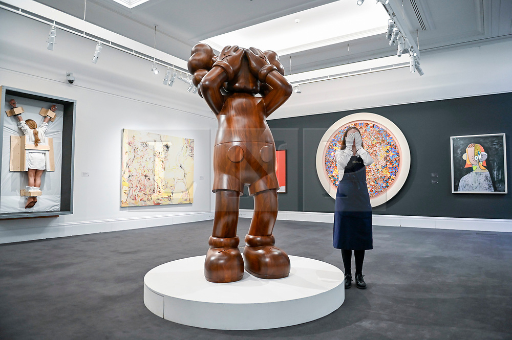 © Licensed to London News Pictures. 07/02/2020. LONDON, UK. A technician poses next to ''At This Time '' by Kaws, (Est. £700,000 - 900,000). Preview of Sotheby's Contemporary Art Sale in their New Bond Street galleries.  Works by artists including Francis Bacon, Yves Klein, Jean-Michel Basquiat and David Hockney will be offered for auction on 11 February 2020.  Photo credit: Stephen Chung/LNP